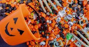Orange pumpkin pail spilling Halloween candy