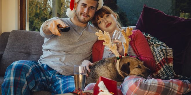 Young couple at home with their pet dog at Christmas time.