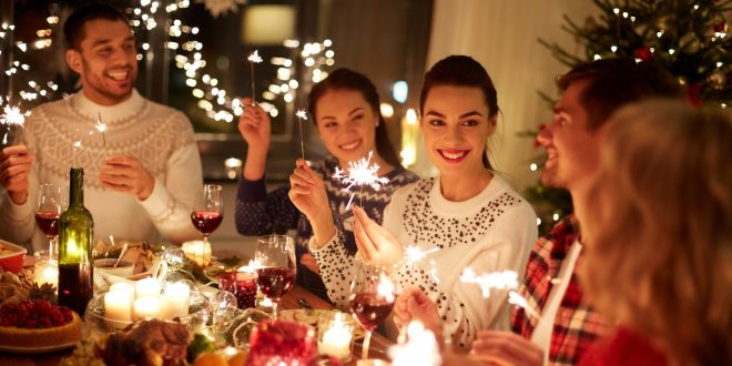 happy friends with sparklers celebrating christmas