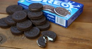Many OREO sandwich cookies with pack on wooden background